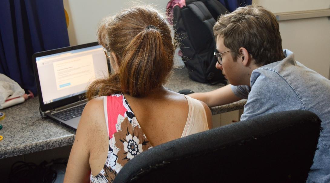 Un estudiante aprendiendo a utilizar el ordenador con un voluntario en Sudáfrica.
